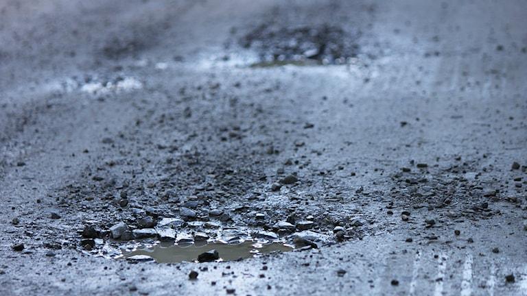 Grusväg med vägskador/potthål