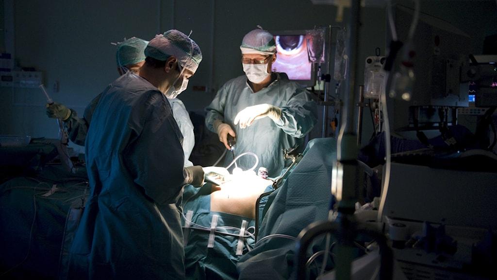 Tre blåklädda kirurger står vid en person som ska opereras. En lampa lyser på patientens kropp.