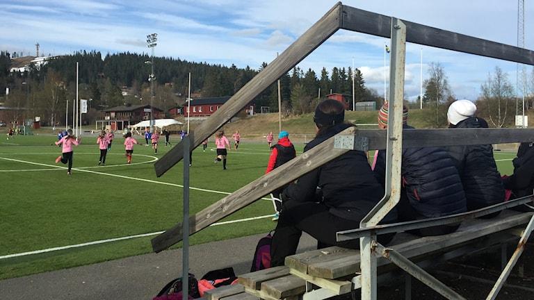 Läktare med föräldrar som tittar på en fotbollsmatch mellan två unga tjejlag. På den här matchen var stämningen god och inga föräldrar skrek på domaren.