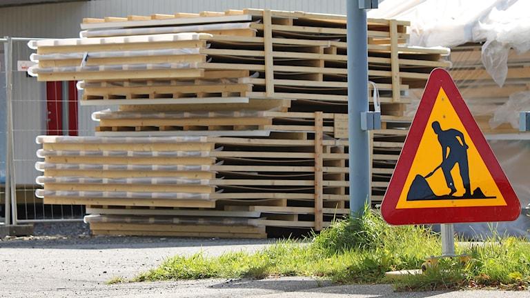 Byggarbetsplats med byggmoduler och varningsskylt
