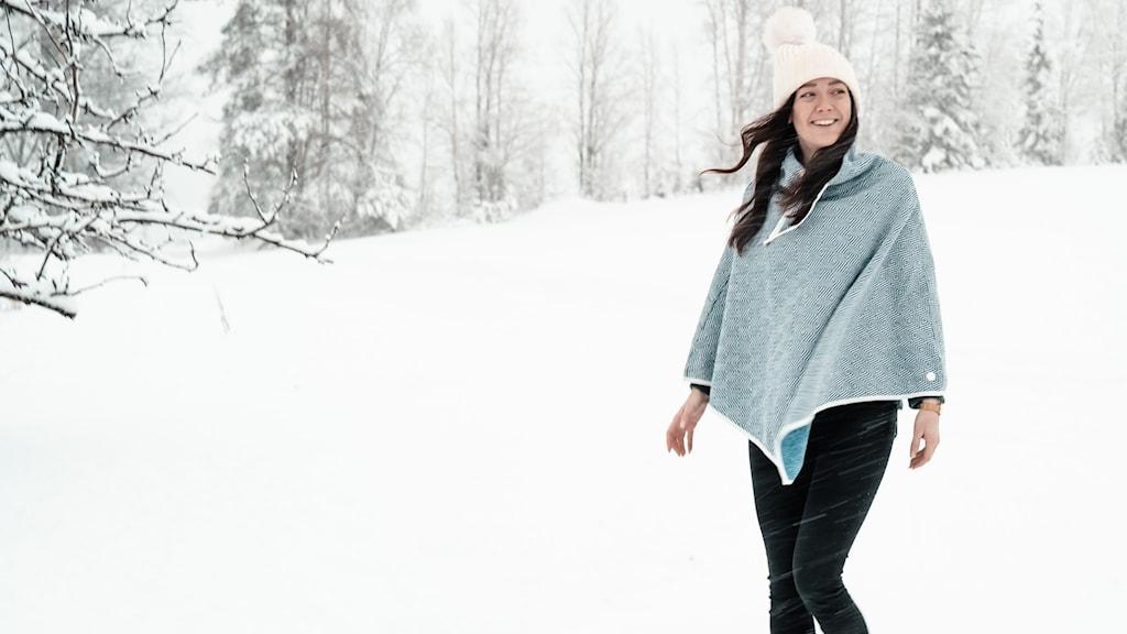 En leende tjej i toppluva och poncho ute i snöyran