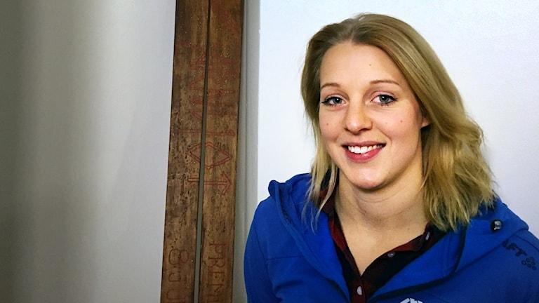 kvinna med blont hår och blå jacka