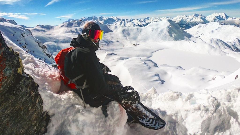Snowboardåkare med svarta skidkläder och rödglänsande skidglasögon sitter i en snöig brant på en fjällsida med höga fjälltoppar runtomkring