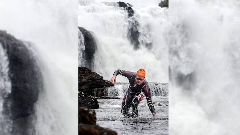 En man i våtdräkt som precis kämpat sig igenom ett vattenfall.