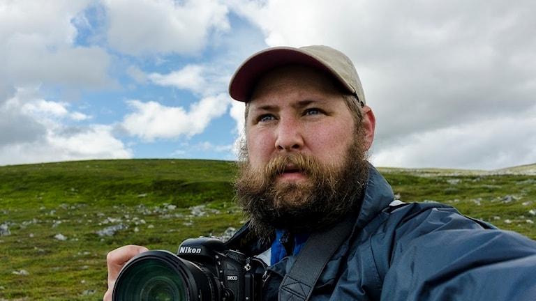 Porträttbild av man med kamera i handen och keps på huvudet, utomhus framför ett fjäll