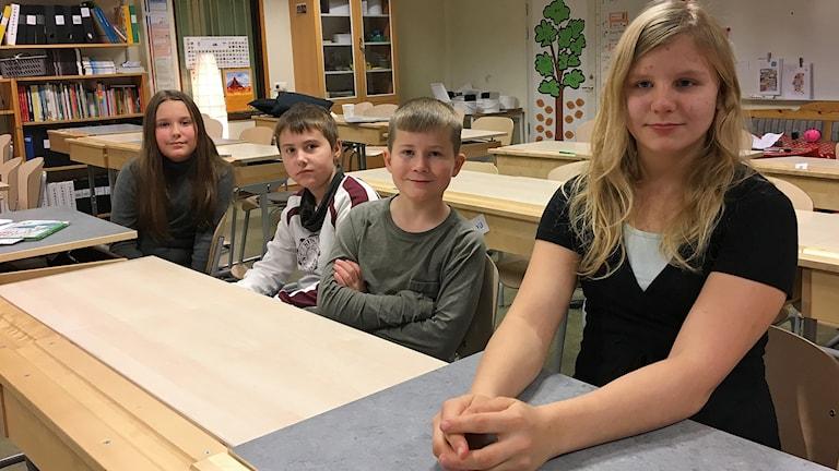 Fyra elever sitter i bänkarna i ett klassrum