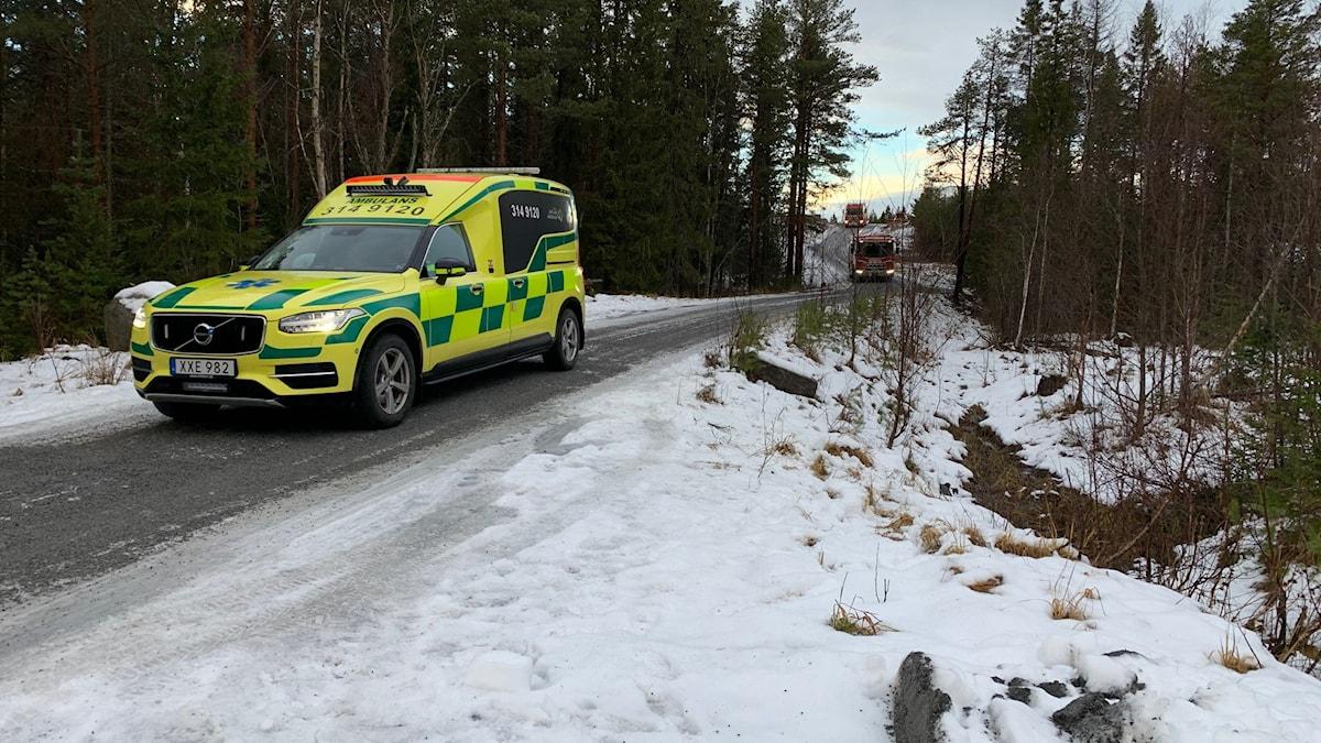 en ambulans på en snöig skogsbilväg