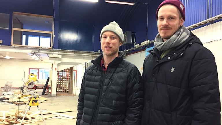 Två män står i en lokal där det pågår ett byggarbete