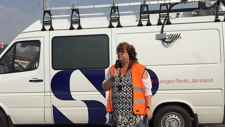 Kvinna med mikrofon framför skåpbil.