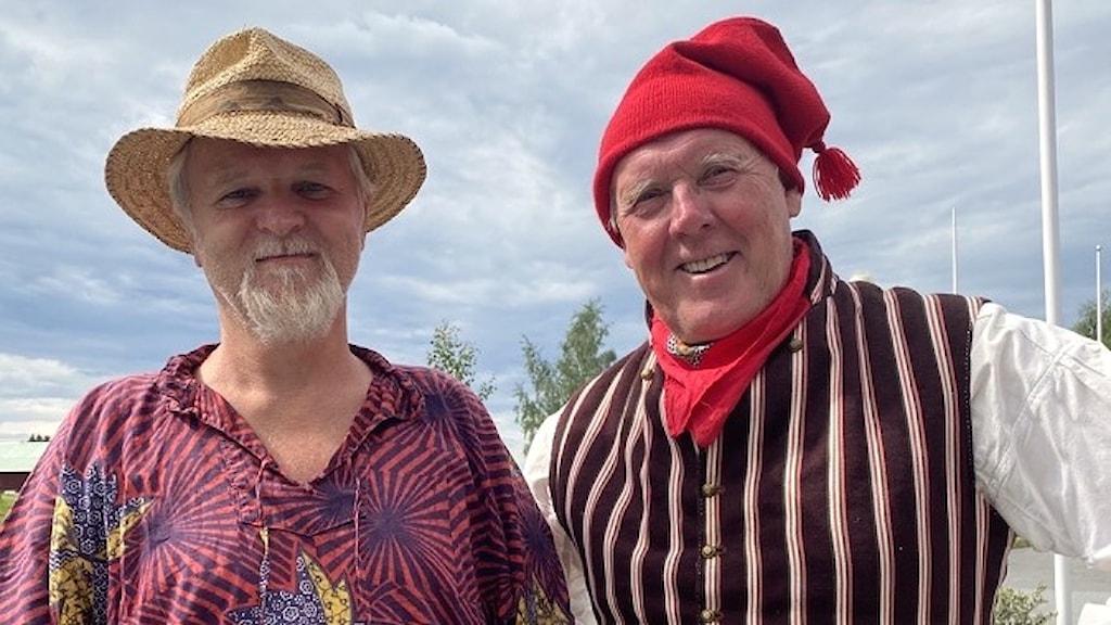 Två stycken äldre herrar, en i stråhatt och en i ovikens folkdräkt.