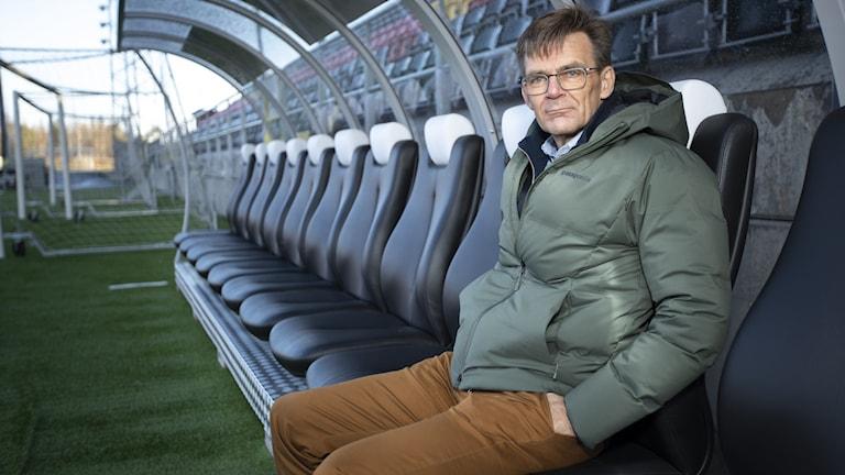 Man i grön täckjacka och bruna byxor sitter på avbytarbänken på en tom fotbollsarena.