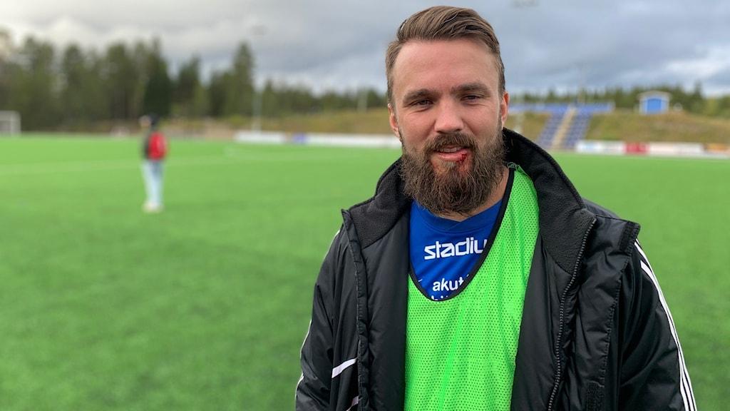 En man med kortklippt hår och yvigt skägg med en svart jacka och en neongrön väst vid en fotbollsplan