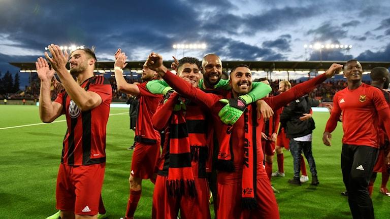 Flera fotbollsspelare sträcker upp sina händer och applåderar efter avslutad match.