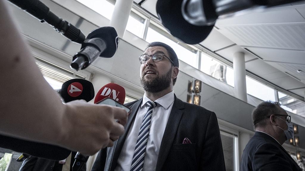 En man i svart kostym med vit skjorta framför ett pressuppbåd i regeringshuset