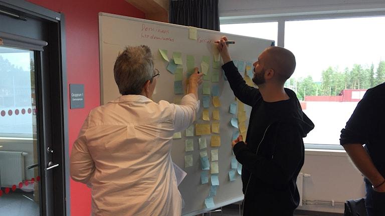 Två personer skriver på whiteboard-tavla med lappar på