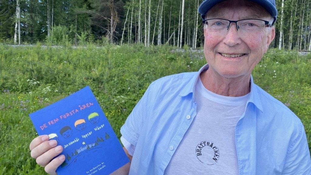 Äldre man i blå keps som håller upp en bok