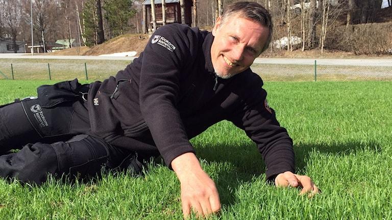 En leende man ligger i det gröna gräset. Kokoms kommuns Idrottsanläggningsvaktmästare Michael Olofsson visar stolt upp den spelklara fotbollsplanen med riktigt gräs.