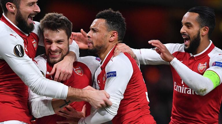 Rödvitklädda manliga fotbollsspelare kramar om varandra