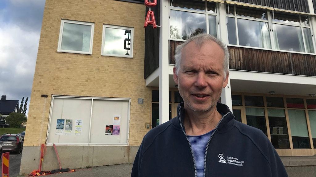 En tunnhårig man utanför ett aktivitetshus med blårandig t-shirt och en mörkblå kofta utan på