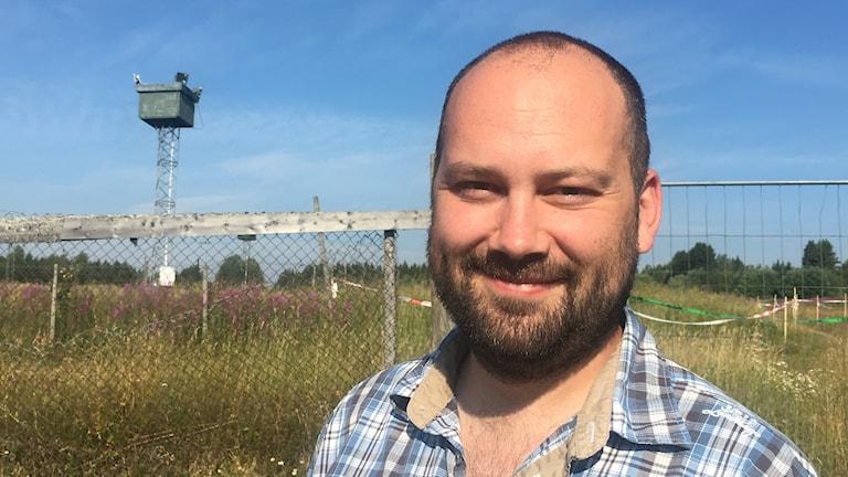 Mörkhårig kortklippt man med skägg i 35-års åldern tittar rakt in i kameran och ler. I bakgrunden syns Gräfsåsens Motorstadion.