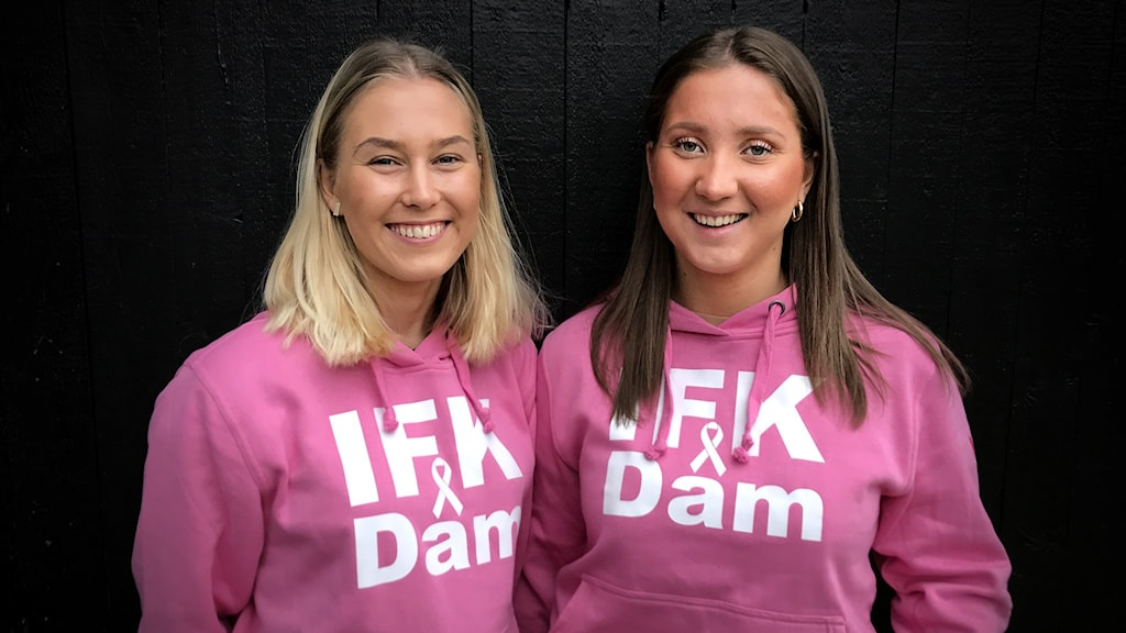 Två tjejer med långt hår i rosa collegetröjor.