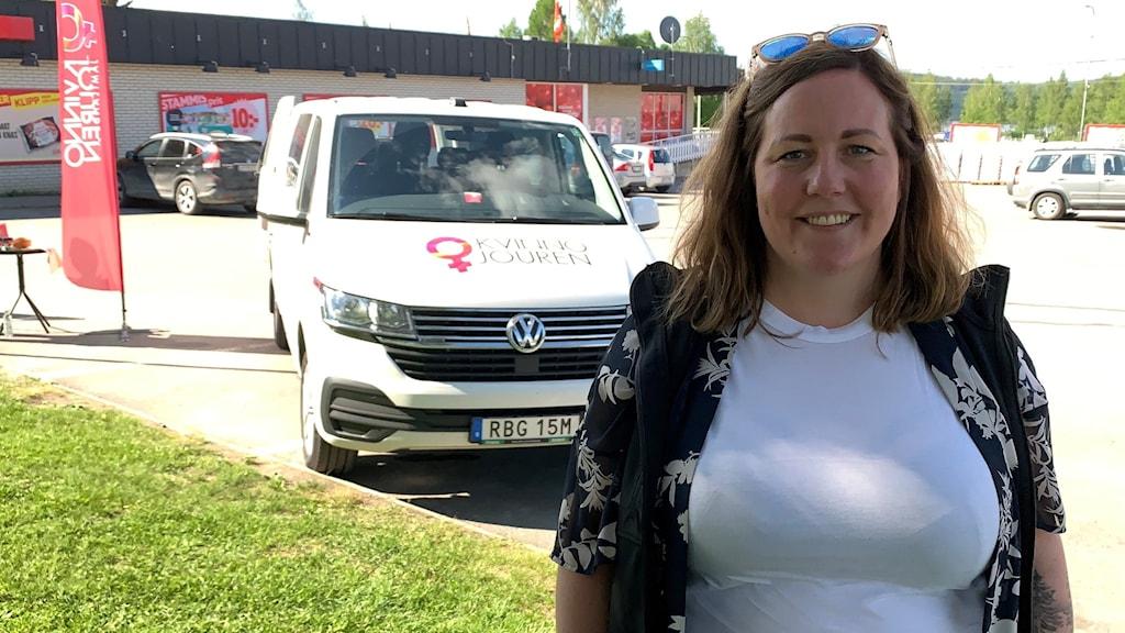 en kvinna i vit tshirt på en parkering framför en liten buss med texten kvinnojouren