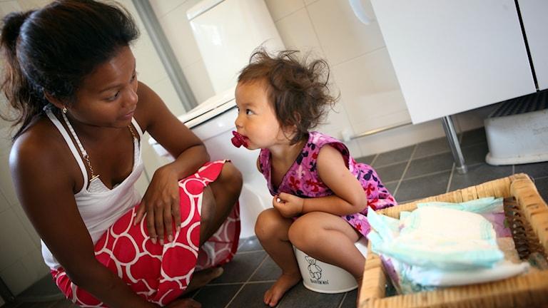 Liten flicka tränar på att sitta på pottan och mamman sitter på huk bredvid