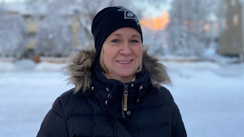 En leende kvinna i svart mössa och jacka ute i snötäckt landskap