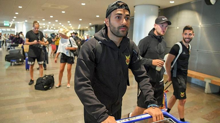 Ung man med bakåtvänd keps och huvtröja går med bagagevagn på en flygplats