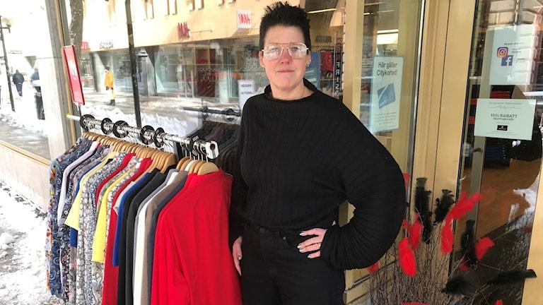Kvinna med mörkt, kort hår står utanför butiksentré med ett klädställ bredvid sig ute på gatan