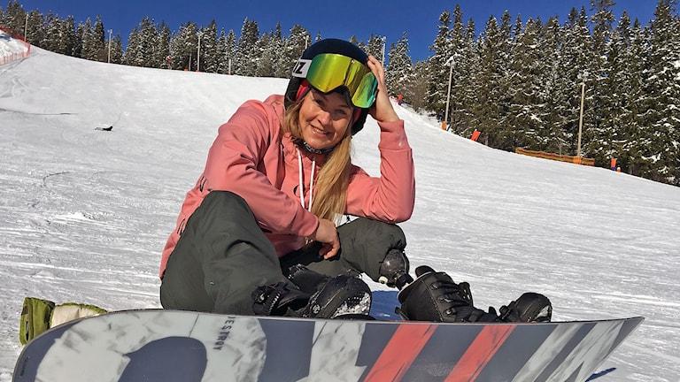 kvinna med snowboard, rosa jacka och skidglasögon i slalombacke