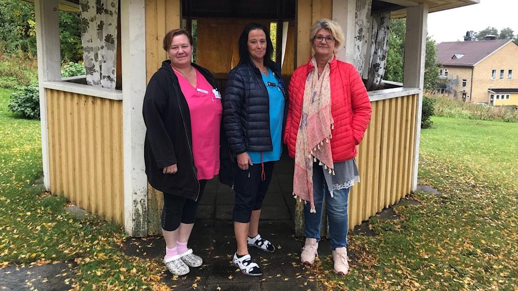 Tre kvinnor vid ett runt hus på en gräsmatta
