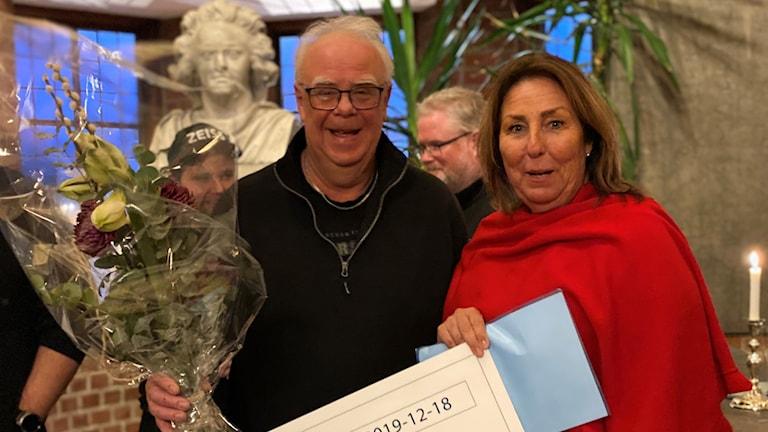 Glad medelålders man som mottar diplom av leende kvinna i Östersunds rådhus
