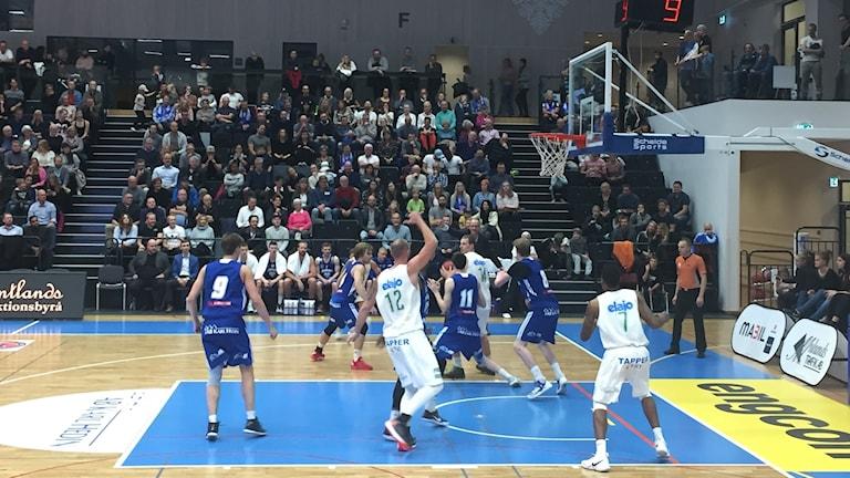 Basketspelare iklädd blåa och vita dräkter spelar en basketmatch inför hundratals åskådare.