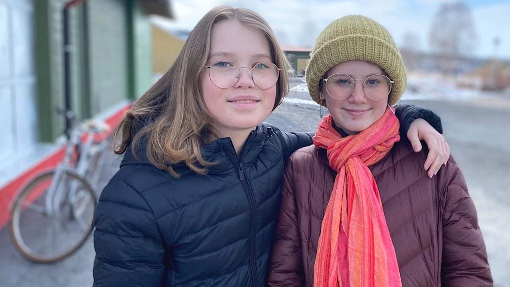 Två tolvåriga tjejer. Den ena har på sig mörkblå vinterjacka, den andra har lila jacka, rosa halsduk och grön mössa.