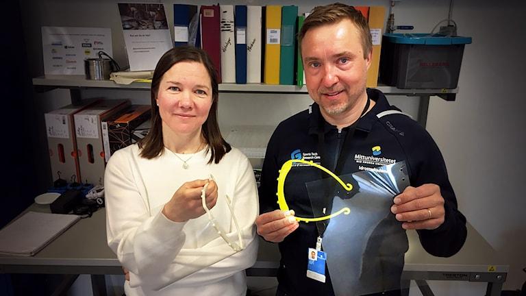 En kvinna och en man visar upp 3D-printade visirhållare med visir av OH-plast.