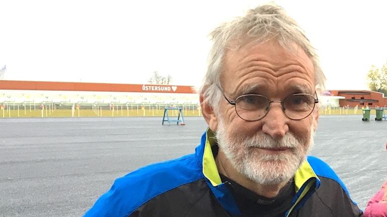 Man med grått hår och glasögen med skylt bakom där det står Östersund