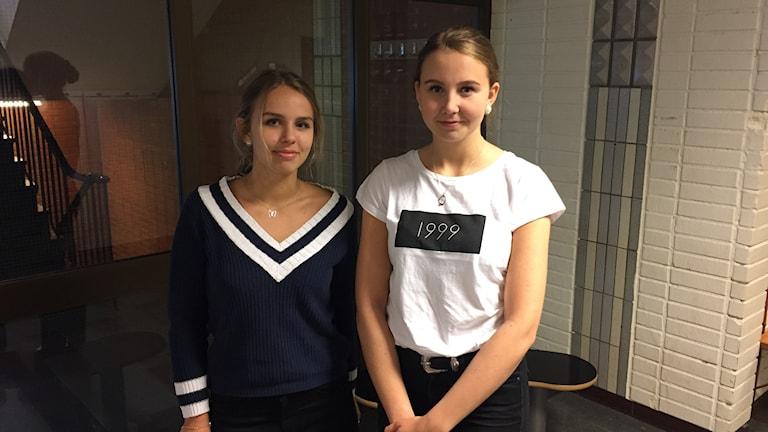 Två tjejer står bredvid varandra i skolmiljö