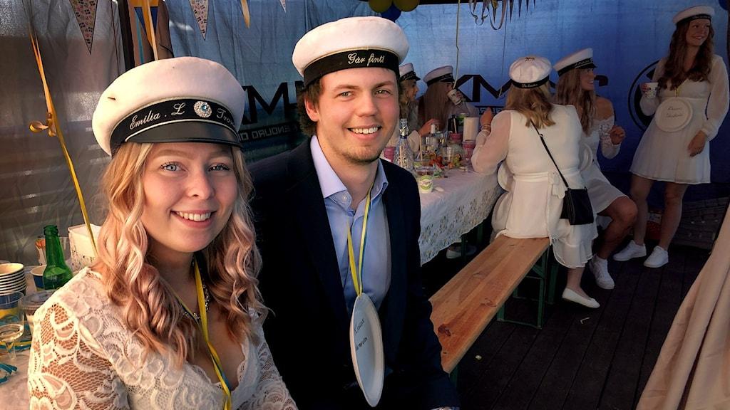 Man och kvinna i studentmössor under en champagnefrukost.