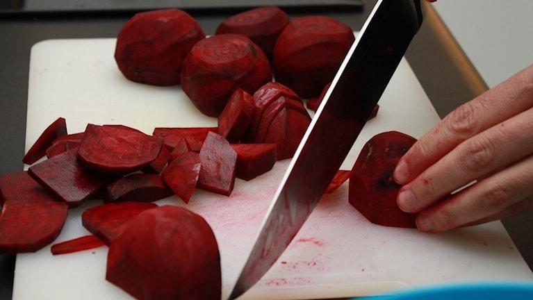 Skär med kniv i rödbetor på skärbräda.