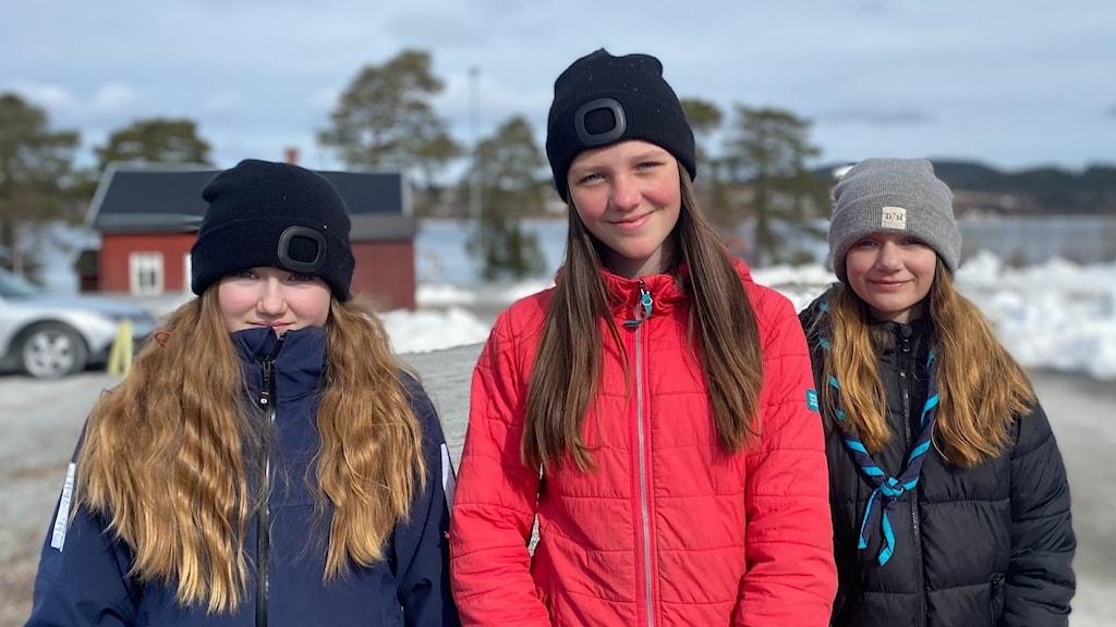 Tre tjejer med långt hår och jackor står på en parkering ned snö i bakgrunden.