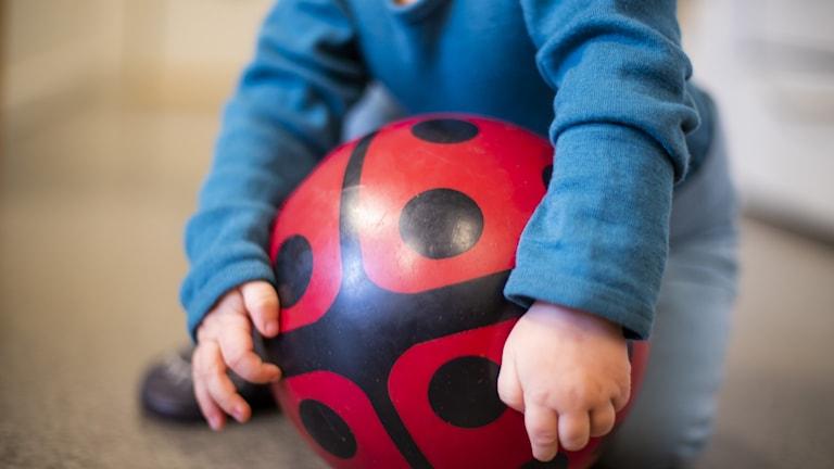 Närbild på ett litet barn som sitter och håller i en röd boll med svarta prickar.
