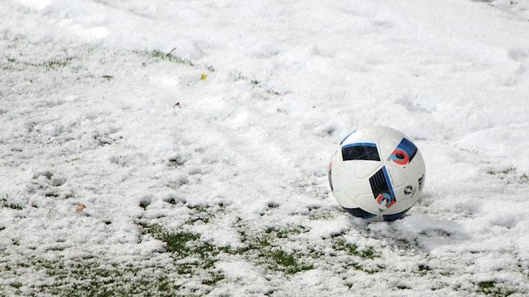 Fotboll i snö på konstgräsplan