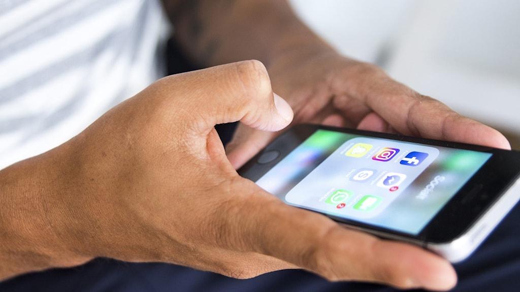 Manshänder som håller i en mobiltelefon
