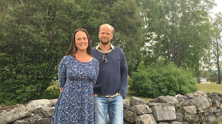 En kvinna och en man står bredvid varandra framför en stenmur.