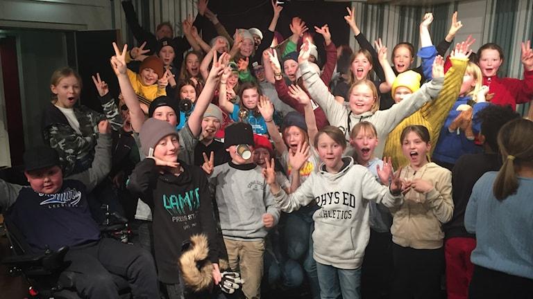 Glad skolklass sträcker upp händerna