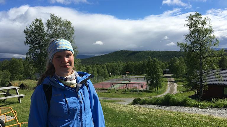 Kvinna i täckjacka står på en höjd med kullar täckta av skog i bakgrunden.