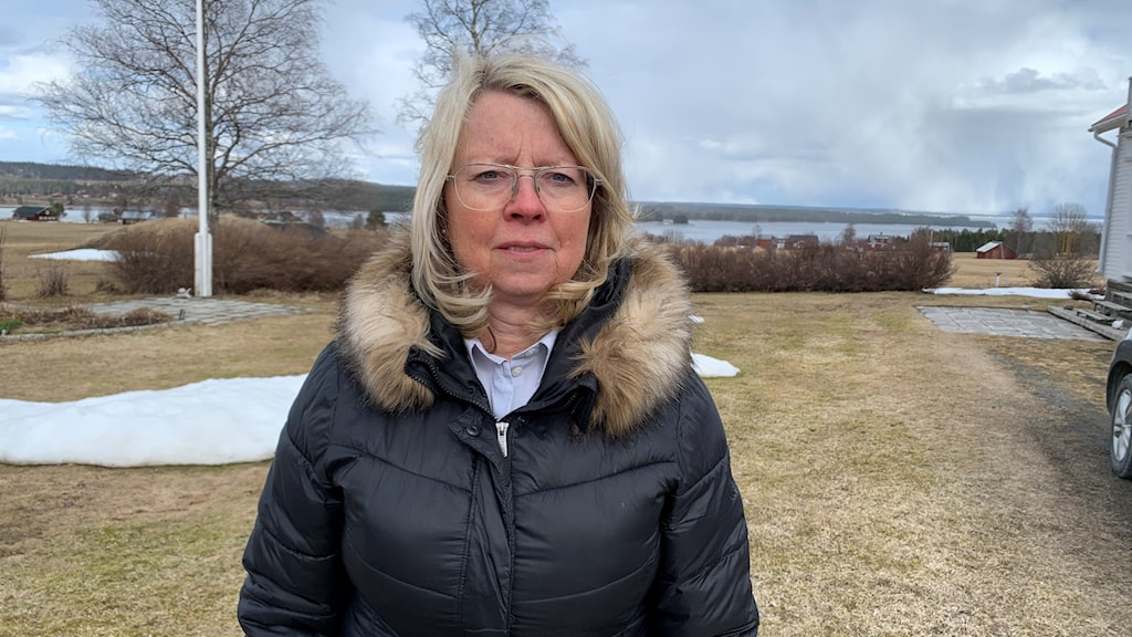 Blond kvinna ser sammanbiten ut. står utomhus i brunt vårlandskap
