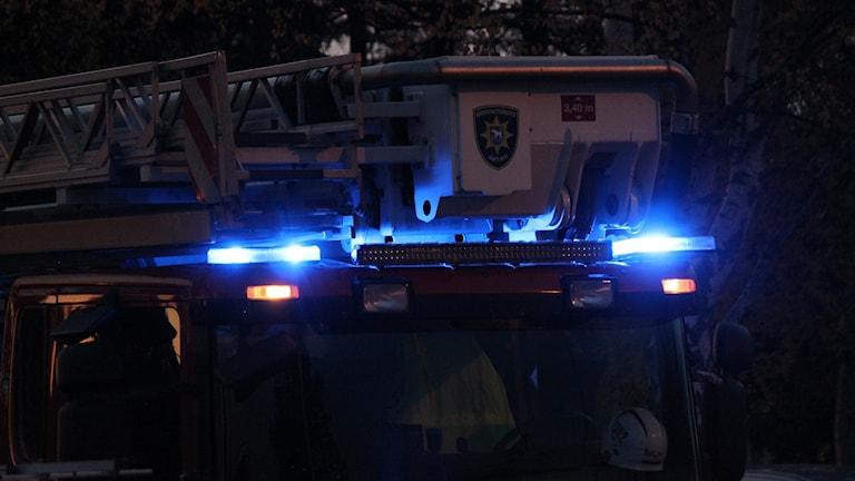 Räddningstjänstens stegbil med blåljus påslagna