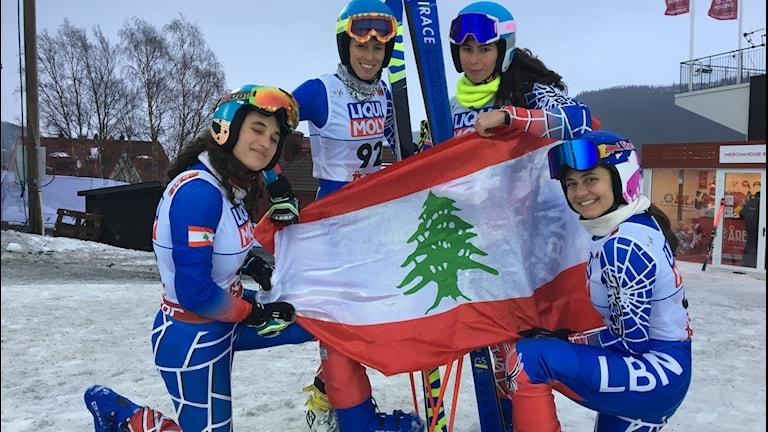 Fyra skidåkare håller upp den libanesiska flaggan.